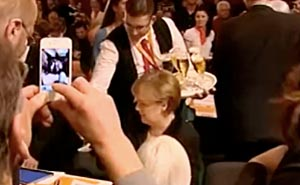 Angela Merkel gets Beer Shower. Still from video
